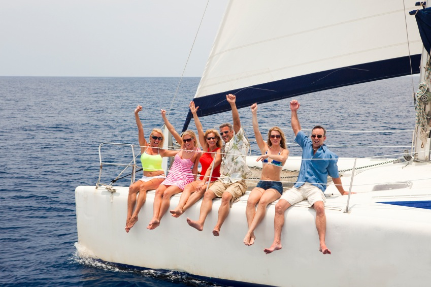 Group of friends yelling and enjoying sailing catamaran